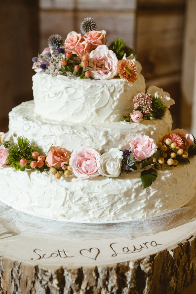 Scott's mother designed our cake, which she topped with fresh flowers , berries, and greenery - photo by James Cripps
